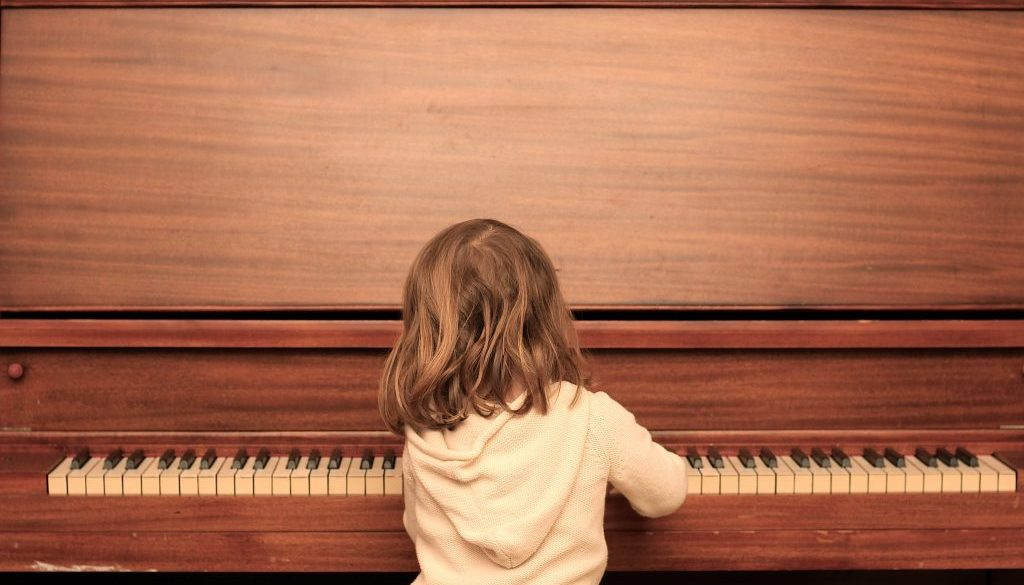 photography of girl playing piano